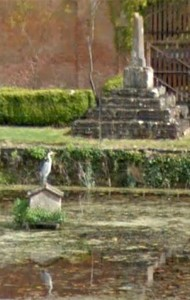 A heron poses in front of the ancient cross on the lily pond