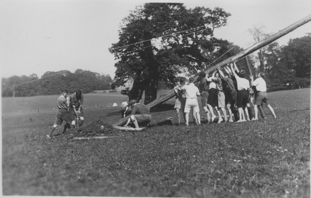 Scouts erecting a camp flagpole below Penpole Woods in about 1937-38 with Kings Weston House in the background.